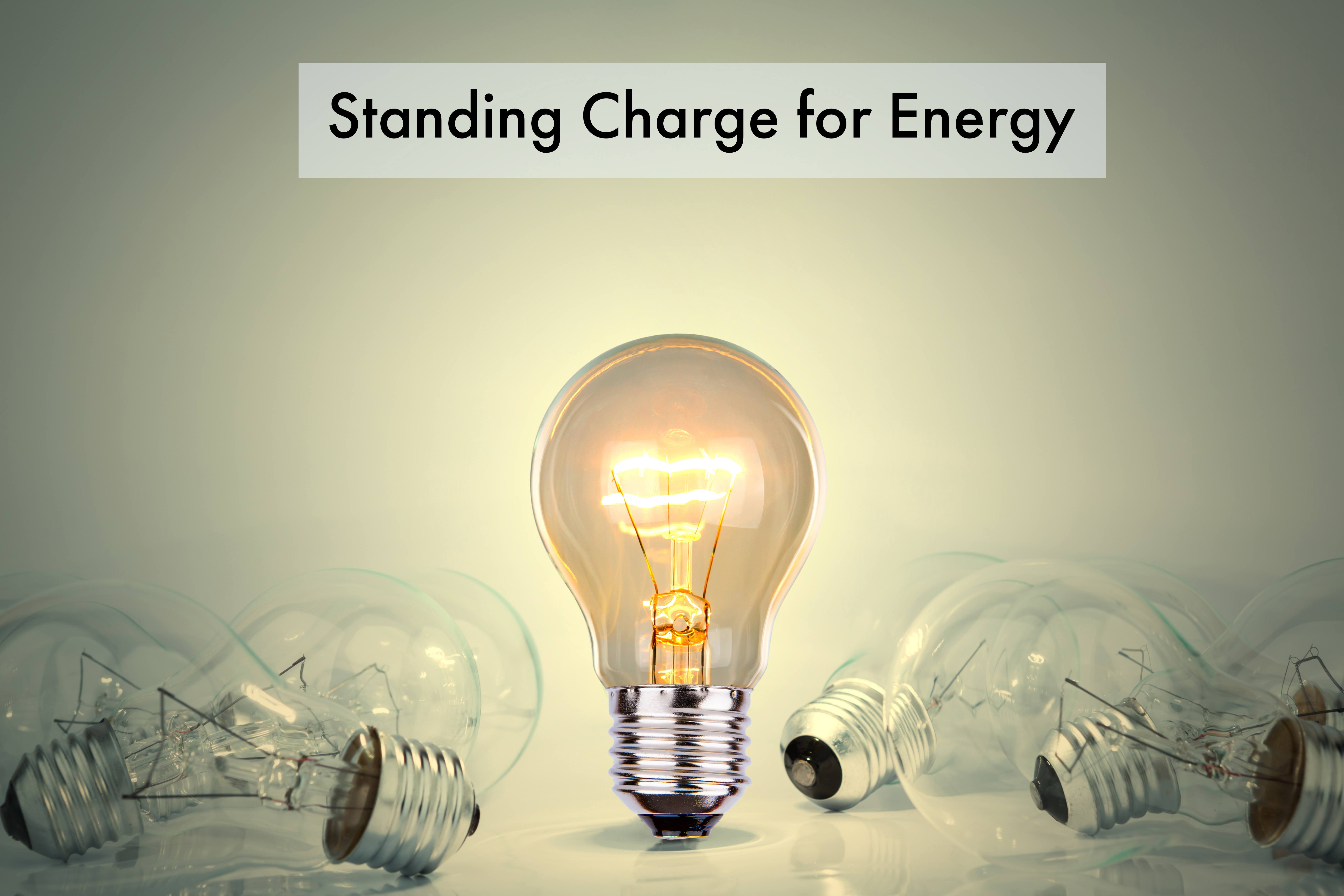 standing charge for energy written above multiple lightbulbs with only one stood up glowing, all the rest are on their sides not glowing.
