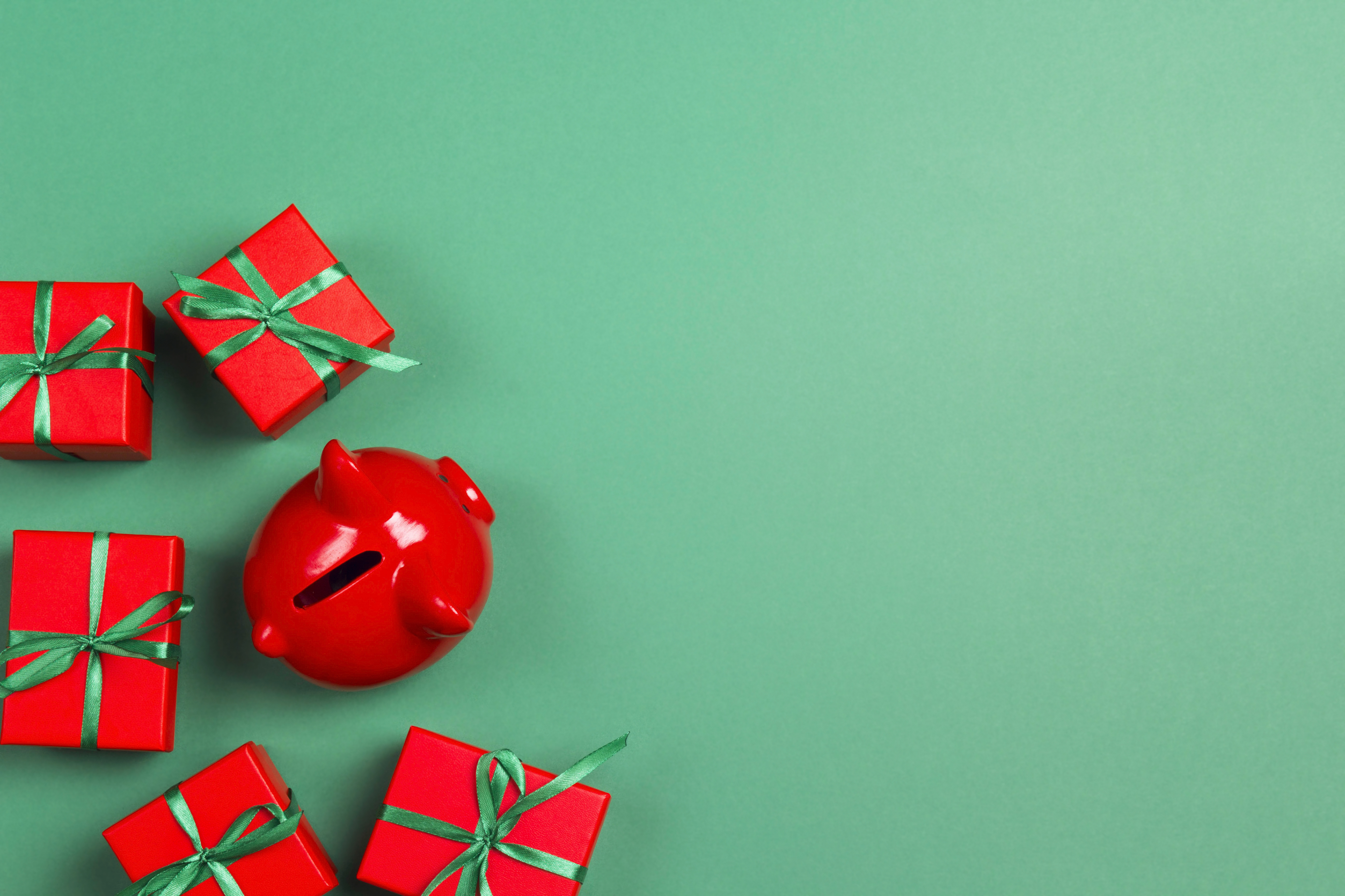 Piggy bank and christmas gifts on green background. Saving money and buying Xmas gifts. Top view with copy space.